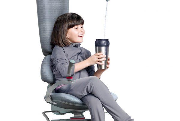 na zdjęcie dziewczyna siedzi na fotelu a nad nia dron, który nalewa jej wodę do kubka