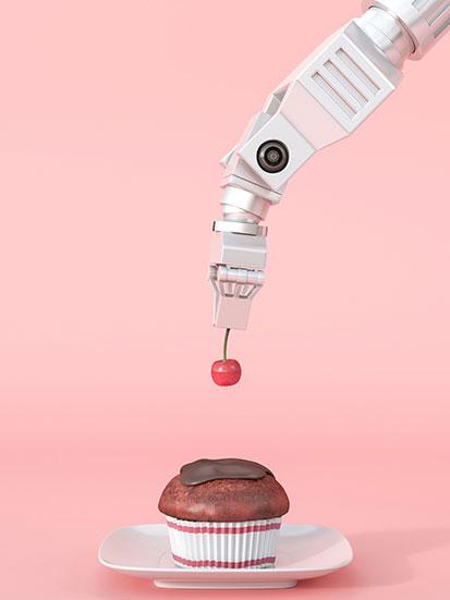 na zdjęciu ramię robota dokłada wisienkę na babeczkę