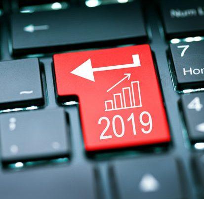 na zdjeciu jest klawiatura komputera z przyciskiem enter na którym widać napis 2019 i wykres prezentujący wzrost