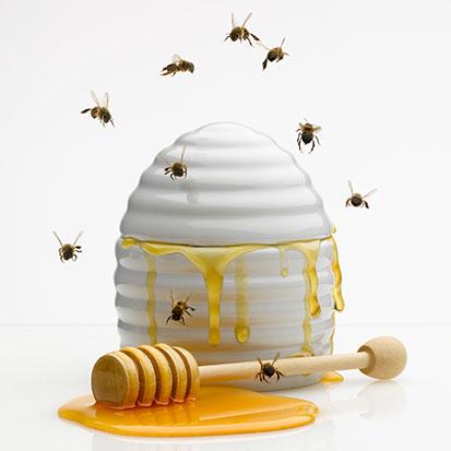 na zdjęicu jest miód, pałeczka do miodu i latające wokoło pszczoły