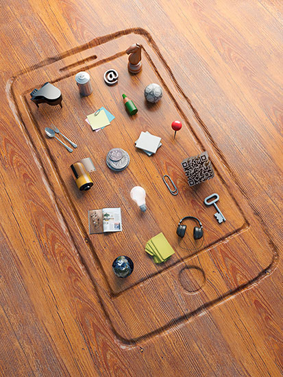 na zdjęicu jest wyryty na blacie kształt smartfona, a w miejscu aplikacji poukładane są różne przedmioty