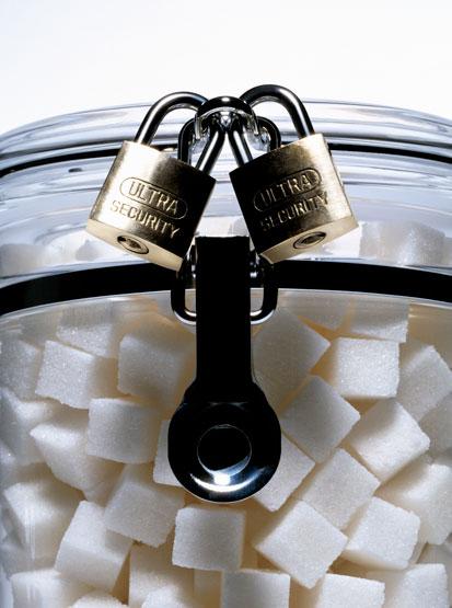 na zdjęciu jest słoik pełen kostek cukru, zamknięty dwoma kłódkami