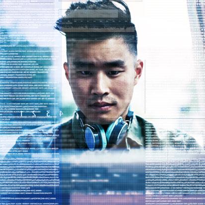 na zdjęciu jest popiersie młodego Azjaty patrzącego w ekran komputera