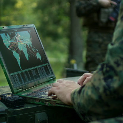 na zdjęciu widać dłonie żołnierza piszącego cos na ekranie laptopa