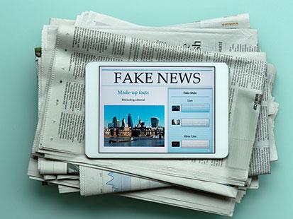 na zdjęciu widać plik gazet a na nim tablet z napisem Fake News