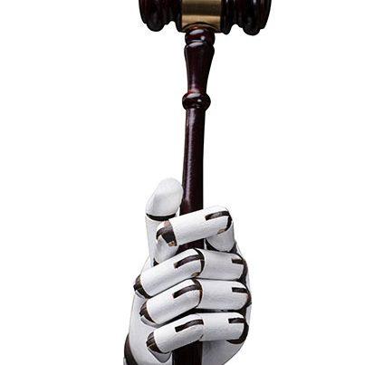 na zdjęciu jest dłoń robota trzymająca młotek sędziowski