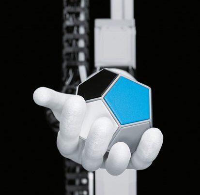 na zdjęciu jest sztuczna ręka trzymająca kostkę