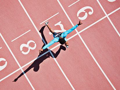 na zdjęciu jest mężczyzna przekraczający linię mety po biegu