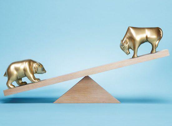 na zdjęciu drewniana waga z figurkami byka i niedziwiedzia ze złota