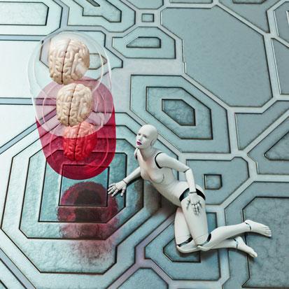 na zdjęciu widać leżącego robota a obok niego tabletkę, wewnątrz której są 3 móżgi