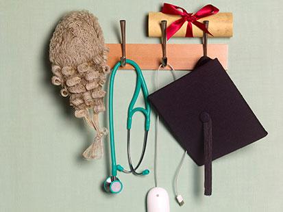 na zdjęciu jest wieszak na ścianie, na nim leży zwiniety dyplom zwiazany wstażką oraz na nim wisi peruka, stetoskop, myszka do komputera oraz biret