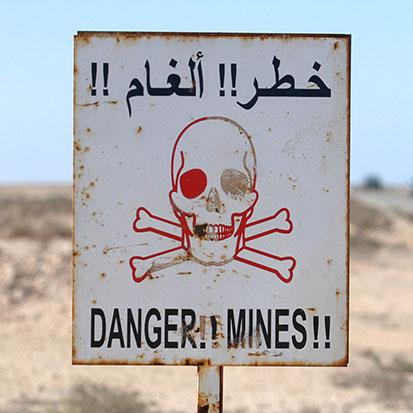 na zjęciu jest tablica z trupią czaszką i napisy niebezpieczeństwo, miny