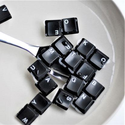 zdjęcie przedstawia talerz z wodą a w nim łyżka i rozsypane klawisze w komputerowej klawiatury