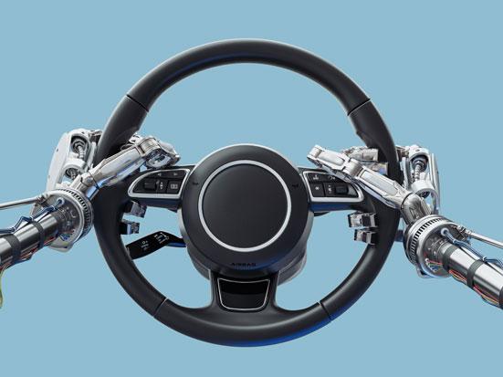 na zdjęciu są ręce robota trzymające kierownice samochodu