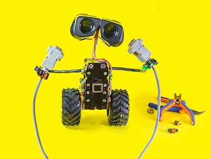 na zdjęciu widać robota, który trzyma kable do komputera. po boku leżą obcęgi