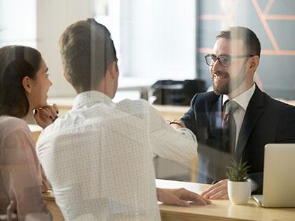 na zdjęciu widać sytuację w banku, gdzie pracownik w garniturze wita sie z dwoma klientami