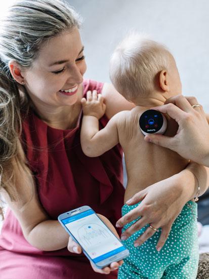 na zdjęciu mama z dzieckiem, mama trzyma w jednej ręce telefon a drugą podtrzymuje dziecko, z boku ręka ojca przykłada do pleców dziecka stetoskop marki StethoMe