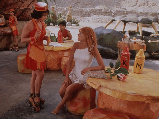 zdjęcie to kadr z filmu Flisntonowie -WIlma i Betty w barze siedzą na stołkach z kamienia