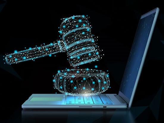 na zdjęciu, na czarnym tle stoi laptop, z profilu, a nad jego klawiaturą unosi się młotek sędziowski narysowany w technice 3D