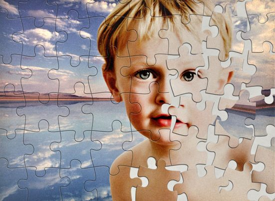 na zdjęciu jest portret dziecka zrobiony z puzzli. cześć puzzli jest rozsypana modyfikując jego twarz