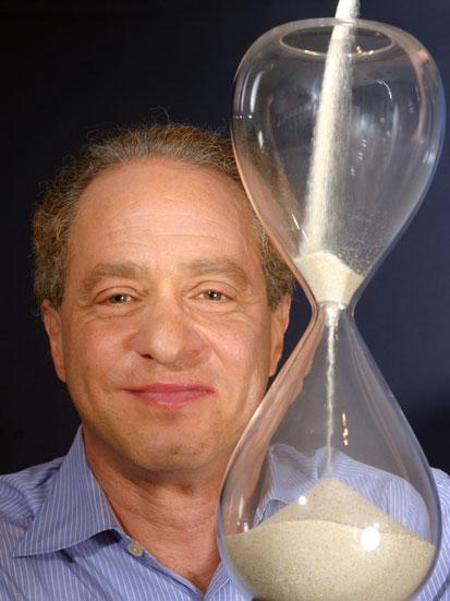 na zdjęciu jest portret Raymonda Kurzweila - obk jego twarzy stoi klepsydra piaskowa