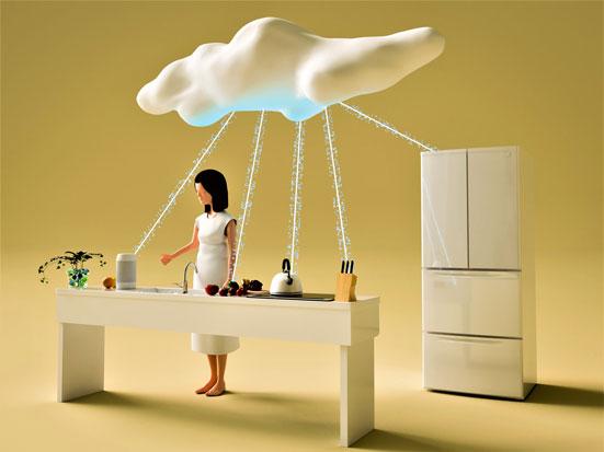 na zdjęciu jest pani za stołem w kuchni a na placie stoi wirtualny asystent oraz leżą warzywa. Ponadto widać czajnik na palniku oraz lodówkę. Nad nią jest chmura połączona ze wszystkimi urządzeniami