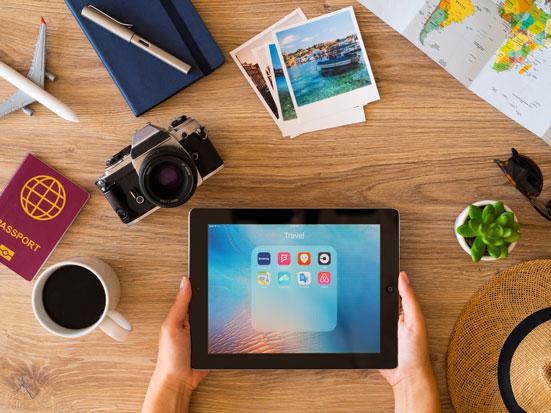 na zdjęciu jest tablet z aplikacjami a wokół atrybuty podróżnika