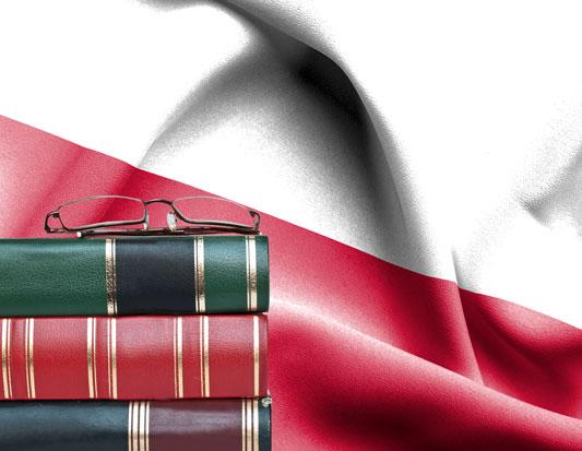 na zdjeciu jest flaga polska i ksiązki na których leża okulary