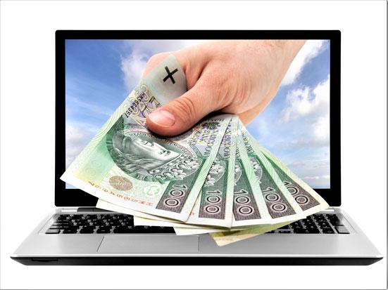 ba zdjęciu jest laptop a w jego ekranie jest wmotowana dłoń z polskimi pieniędzmi
