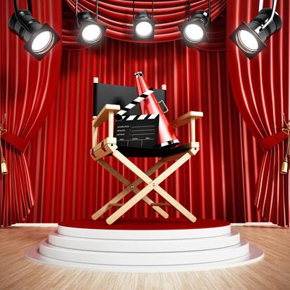 na zdjęciu jest krzesło reżyserskie a na nim leży klaps filmowy i megafon. W tle kurtyna teatralna