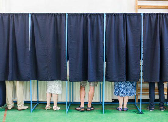 na zdjęciiu sa nogi ludzi, którzy w kabinach wyborczych oddają swój głos