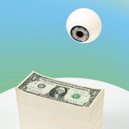 na zdjęciu oko patrzy na plik pieniędzy