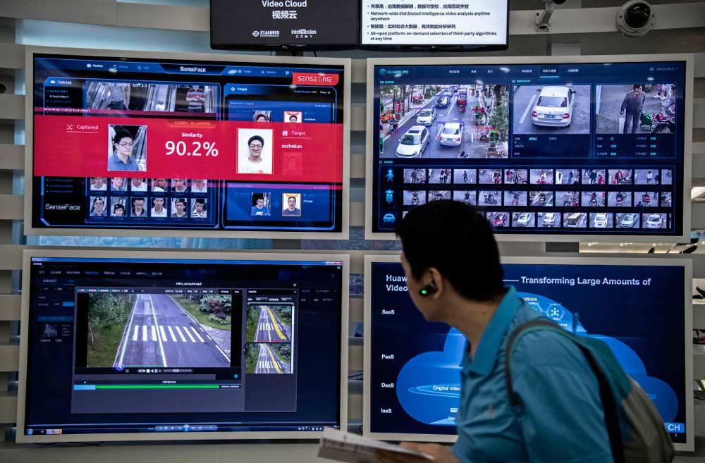 Człowiek patrzy namonitory, naktórychwyświetla się podgląd zkamer monitoringu.