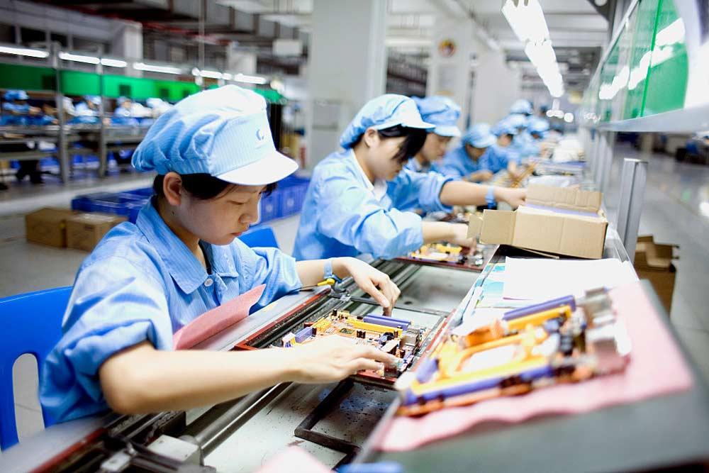Pracownicy fabryki montują elementy komputera
