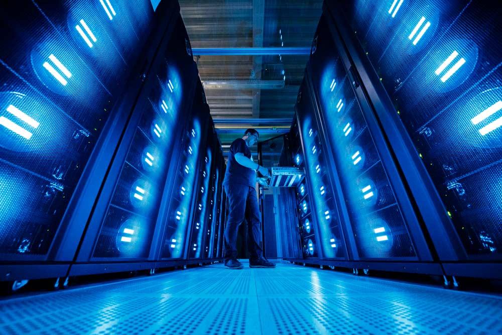 Pracownik centrum danych wyjmuje element zszafy serwera.